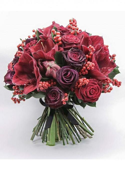 Bouquet di rose rosse, amarillis e bacche rosse.