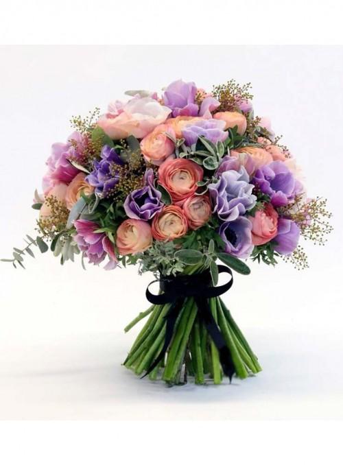Bouquet con ranuncoli rosa, anemoni lilla, rifinito con erbe di stagione.