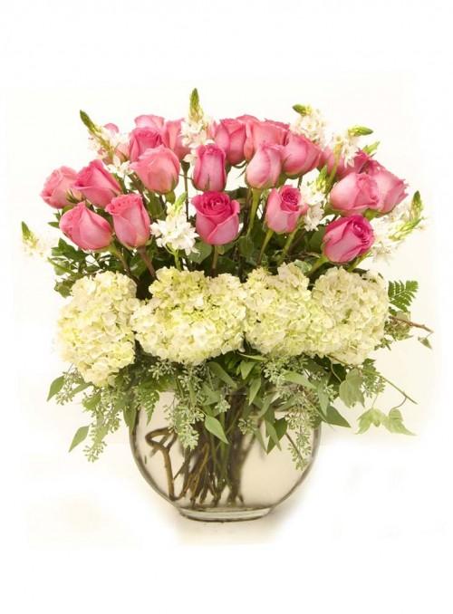 Composizione floreale con rose rosa, ortensie bianche, ornitogalli ed eucalipto.