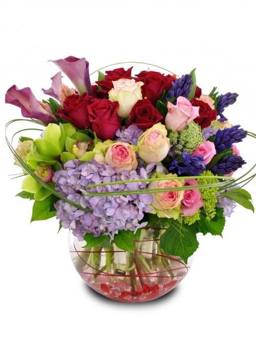 Bouquet con rose rosse, calle lily, rose rosa, giacinti blu, ortensie azzurre e cimbidium verdi.
