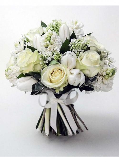 Bouquet con rose bianche, tulipani bianchi, fiori di lillà, rifinito con erbe decorative di stagione.