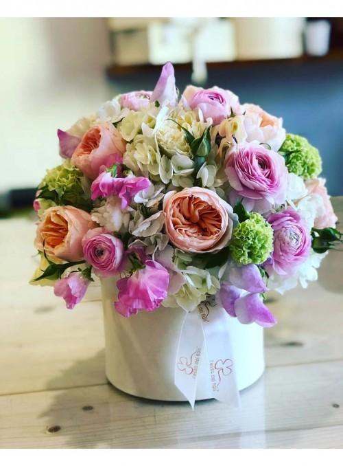 Composizione di rose inglesi, ortensie, lathyrus e viburno realizzata in un box in pelle avorio.