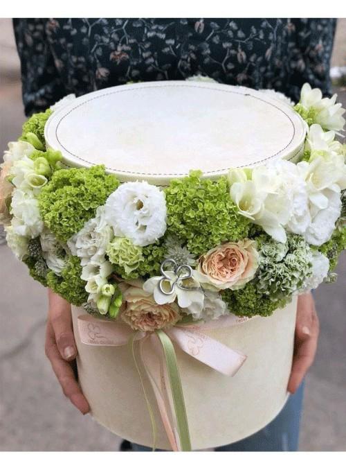 Composizione con fiori bianchi e rosa rifinita con fiori e erbe di stagione in un elegante box tondo in pelle di colore avorio.