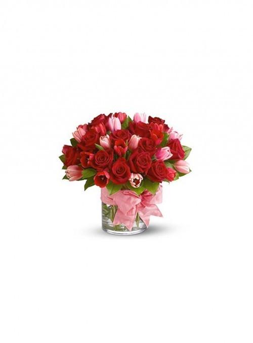 Incantevole bouquet con rose rosse, tulipani rosa e verde decorativo.
