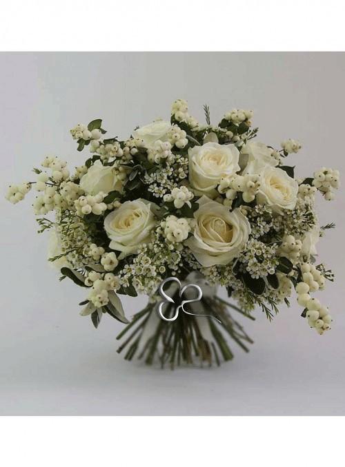 Bouquet con rose bianche, symphoricarpos, wax flower, rifinito con fiori e erbe decorative di stagione.