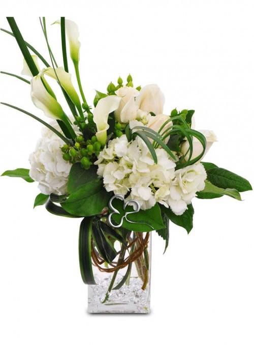 Composizione in vaso con ortensie bianche, ipericum verde, calle bianche e rose bianche.